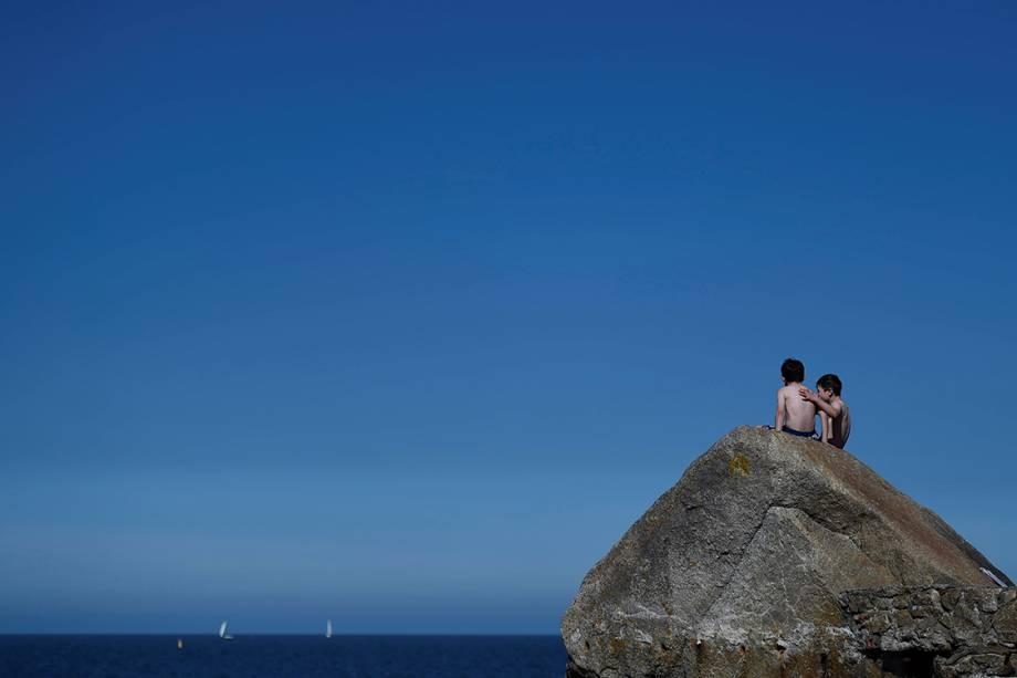 Crianças observam o mar em um dia de calor na cidade de Sandycove, Irlanda - 10/05/2017
