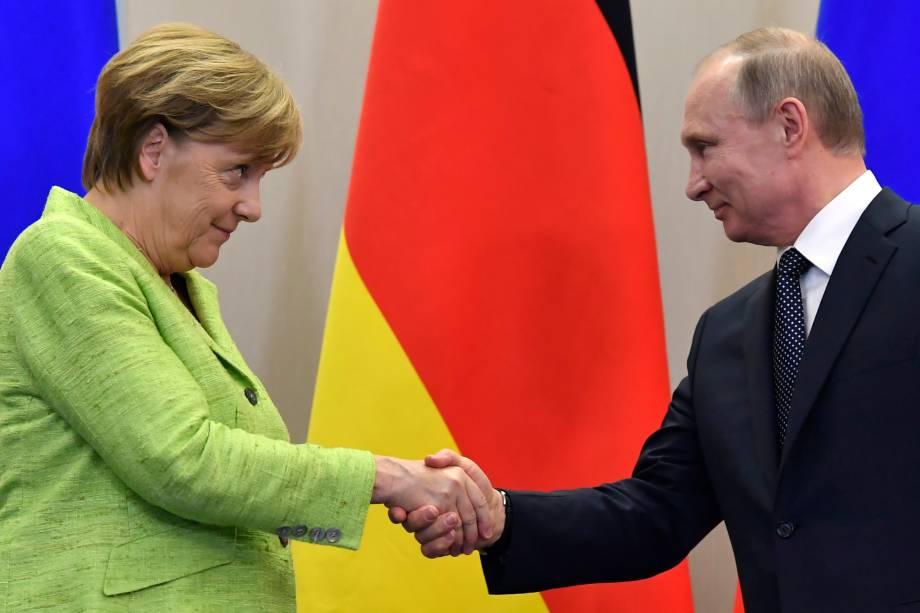 A chanceler alemã, Angela Merkel, cumprimenta o presidente russo Vladimir Putin, durante encontro em Sochi, na Rússia