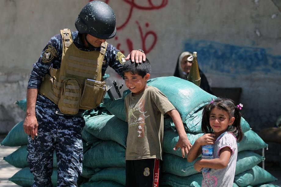 Membro das forças iraquianas brinca com crianças na periferia da cidade velha de Mosul, após área ter sido retomada das mãos dos jihadistas do Estado Islâmico - 24/05/2017