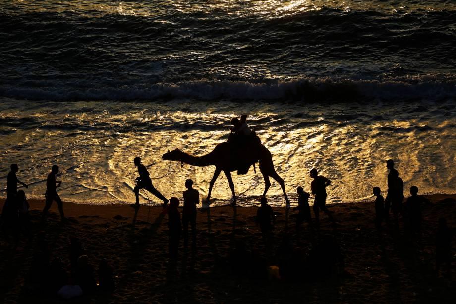 Palestinos aproveitam o fim de tarde na praia durante o pôr-do-sol na Cidade de Gaza - 24/05/2017