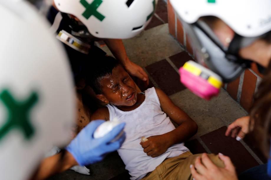 Equipe primeiros-socorros atende uma criança ferida durante manifestação contra o presidente Nicolás Maduro em Caracas, na Venezuela - 24/05/2017