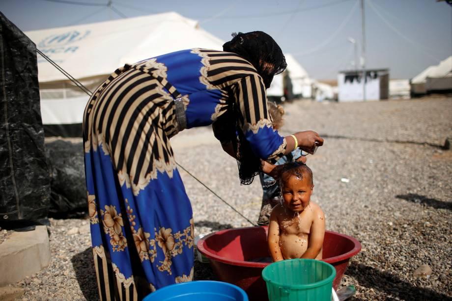 Bebê toma banho no acampamento de Hammam al-Alil que abriga famílias deslocadas das áreas de conflito com o Estado Islâmico, ao sul de Mosul, no Iraque - 10/05/2017