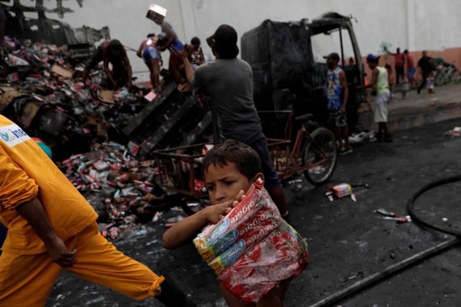 Moradores saqueiam caminhão que foi incendiado por facções criminosas, próximo à comunidade Cidade Alta, no Rio