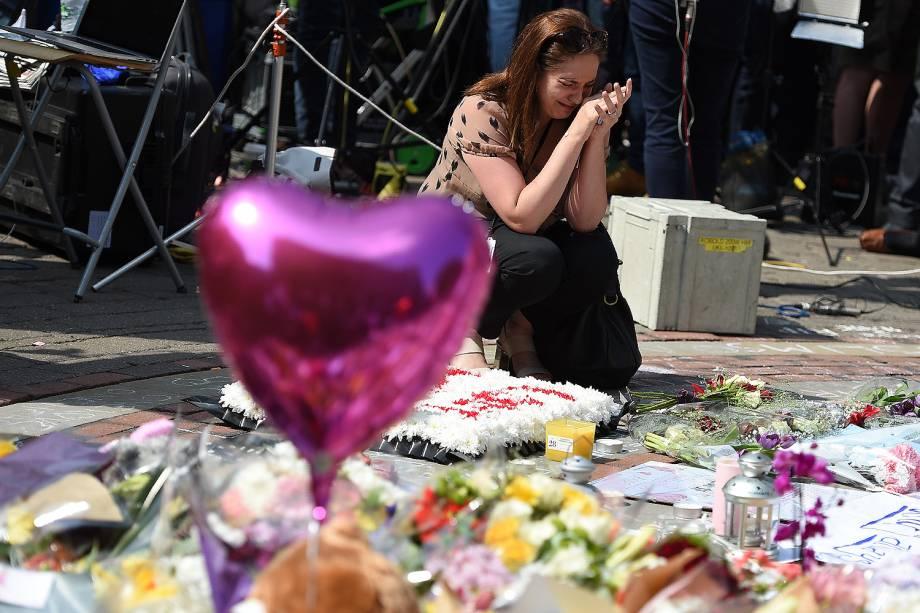 Mulher presta um minuto de silêncio no centro da cidade de Manchester em memória aos mortos no ataque terrorista durante show na Manchester Arena - 25/05/2017