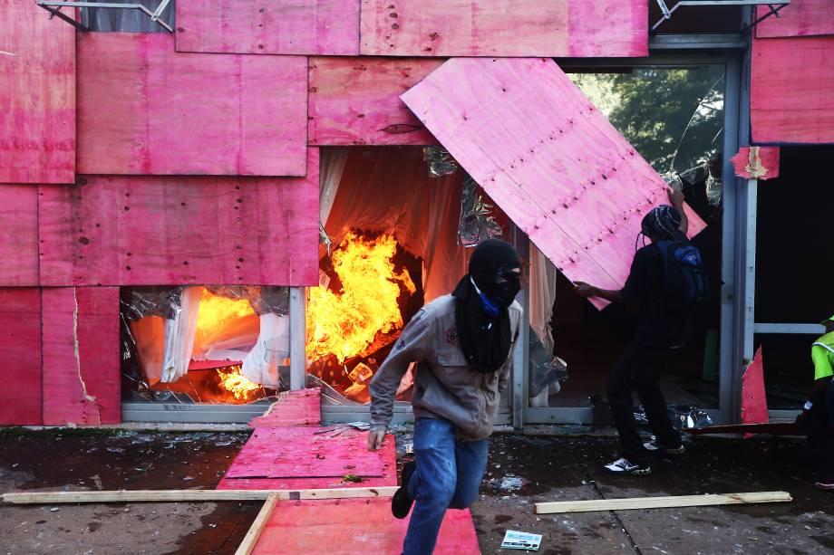 Manifestantes retiram tapumes para colocar fogo no prédio do Ministério da Agricultura, em Brasília, dia de protesto contra as reformas e pela renúncia do presidente Michel Temer - 24/05/2017