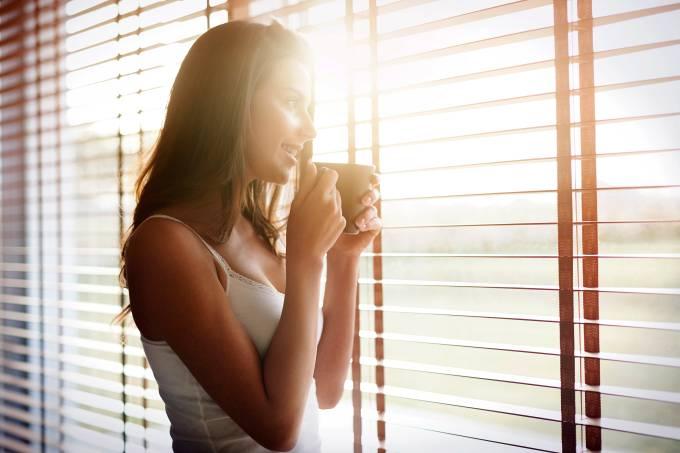 mulher tomando bebida em uma xícara olhando por uma janela