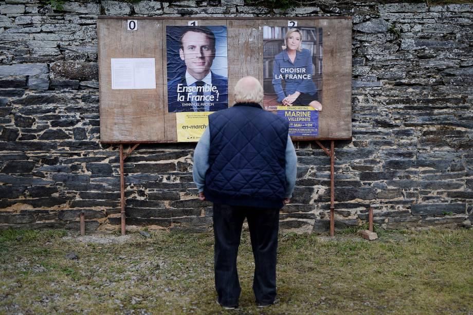 Homem observa cartazes dos candidatos perto de um local de votação durante o segundo turno das eleições presidenciais francesas na cidade rural de Saint-Sulpice-des-Landes - 07/05/2017