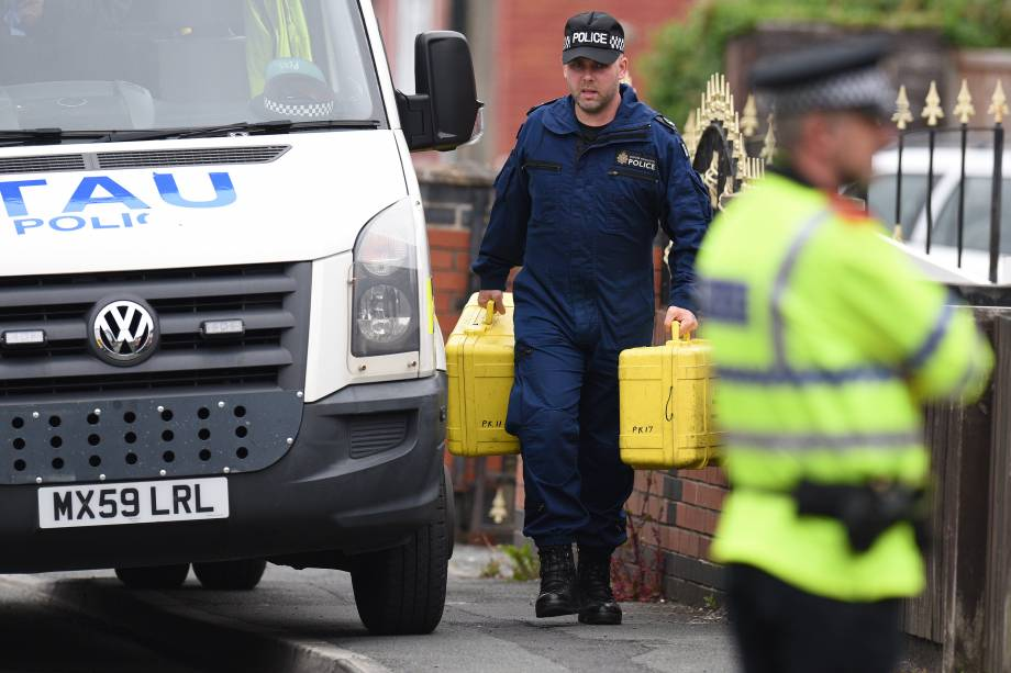 Oficiais de polícia carregam equipamentos forenses enquanto chegam em uma propriedade residencial durante as investigações sobre o ataque terrorista durante show na cidade de Manchester, na Inglaterra - 24/05/2017