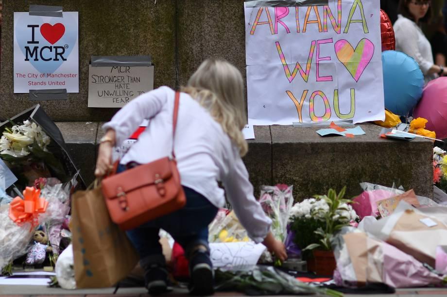Mulher coloca flores em um memorial improvisado às vítimas do ataque terrorista durante show Manchester Arena, na praça de St Ann em Manchester, na Inglaterra - 24/05/2017