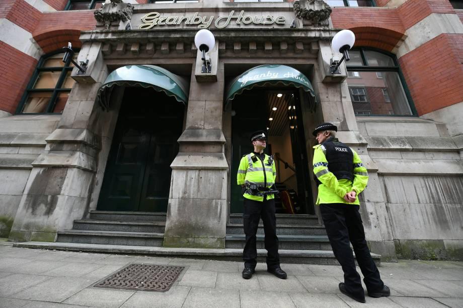 Policiais ficam de plantão em frente ao edifício de apartamentos Granby House em Manchester, durante investigações sobre o ataque terrorista durante um show da cantora Ariana Grade na Manchester Arena - 24/05/2017