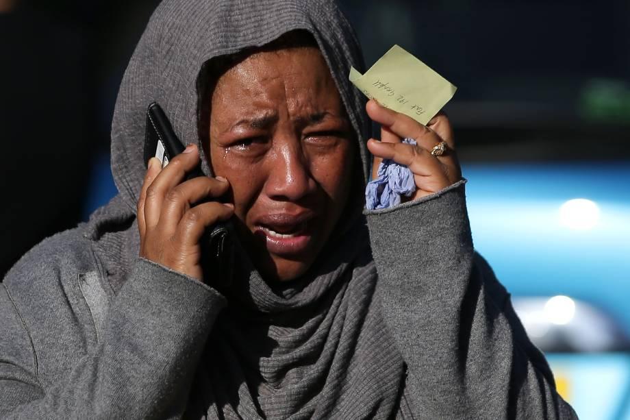 Ao telefone, uma mulher chora desesperada na tentativa de localizar um parente desaparecido e que teria sido afetado pelas chamas do Grenfell Tower, no oeste de Londres - 14/06/2017