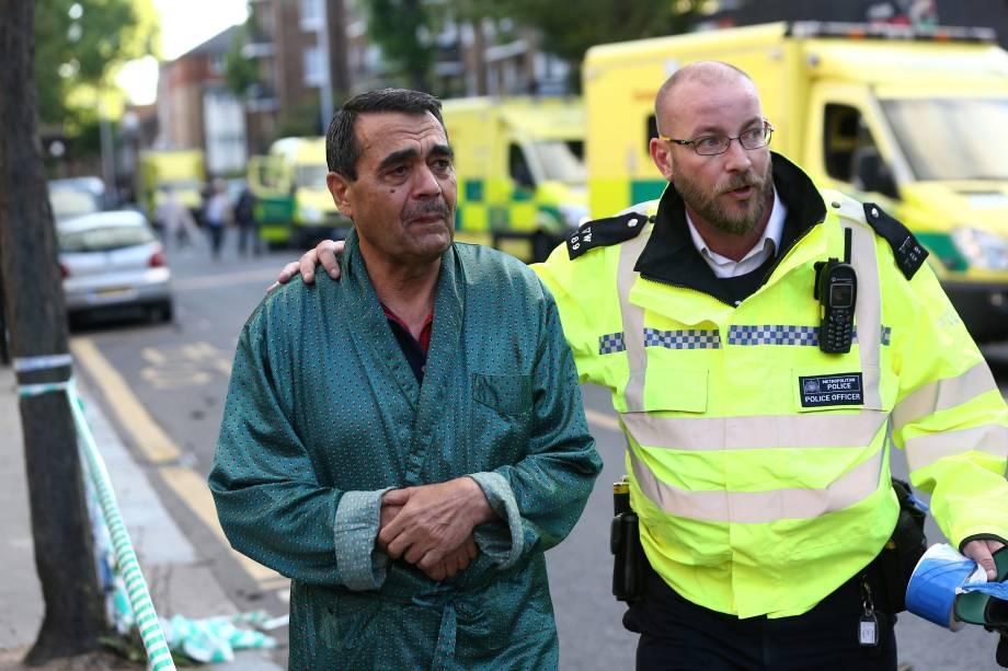 Um policial ajuda a evacuar a área próxima da tragédia ocorrida em Latimer Road, no oeste de Londres - 14/06/2017