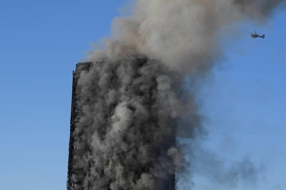 Helicóptero sobrevoa o Grenfell Tower após o fogo ter devastado boa parte do prédio - 14/06/2017