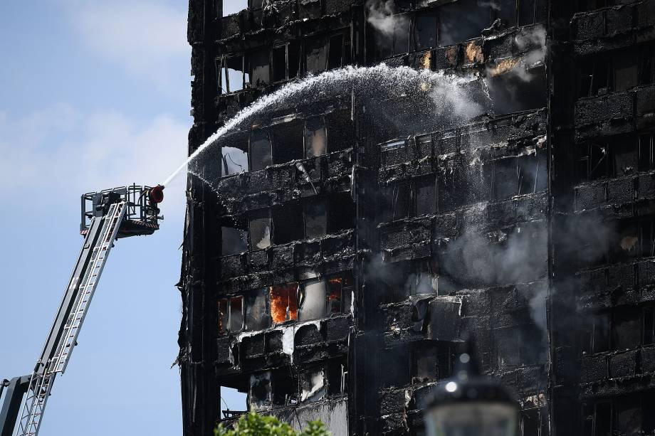 Bombeiros jogam jatos de água para conter as chamas do prédio Grenfell Tower que se iniciou esta manhã na zona oeste de Londres -14/06/2017