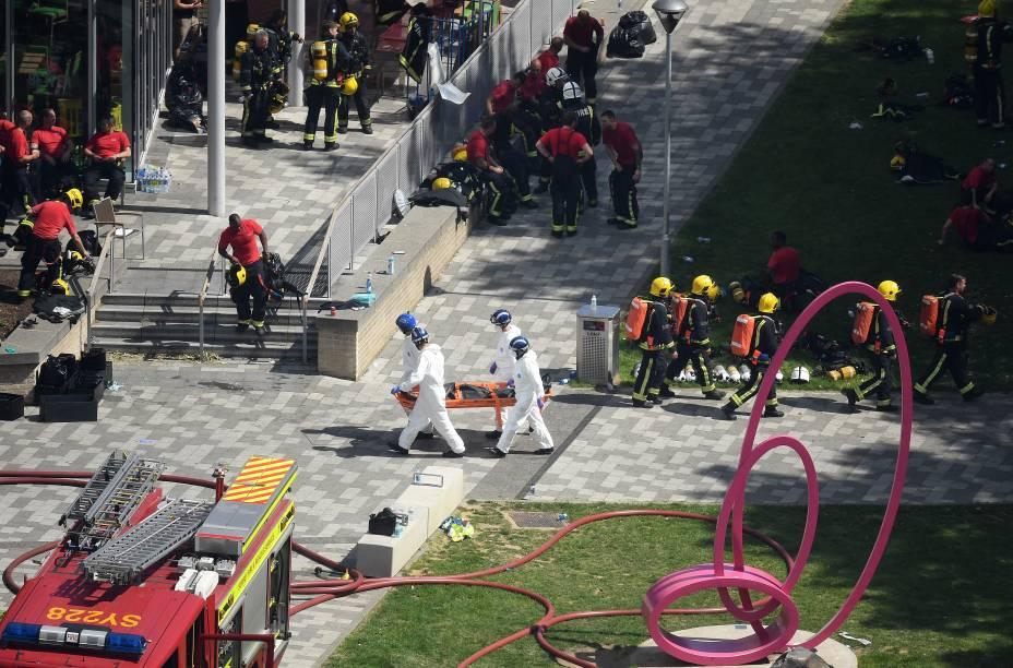 Equipe de emergencia do corpo de bombeiros, policiais e demais ajudantes ao lado do local do incêndio no Grenfell Tower, em Londres - 14/06/2017