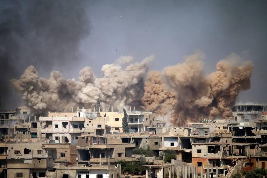 Fumaça sobe dos edifícios após um ataque aéreo em uma área controlada por rebeldes na cidade de Daraa, no sul da Síria - 14/06/2017