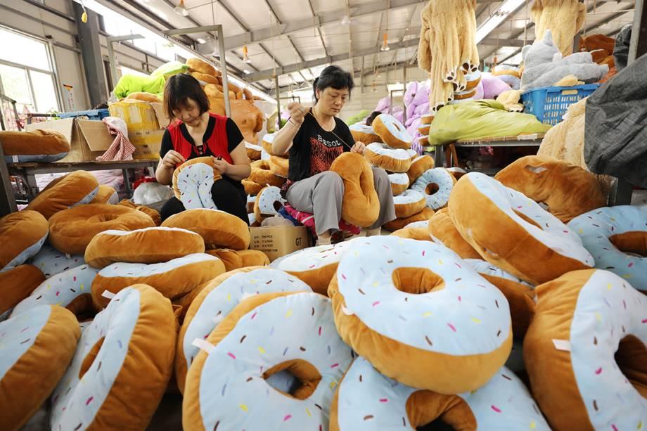 Mulheres trabalham costurando almofadas coloridas na província de Jiangsu, na China - 09/06/2017