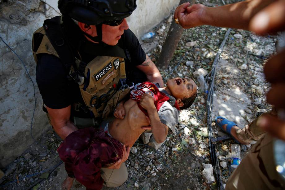 Soldados iraquianos dão gotas de água a uma criança desidratada resgatada na linha de frente, durante os combates entre forças iraquianas e combatentes do Estado islâmico perto da Cidade Velha de Mosul - 14/06/2017