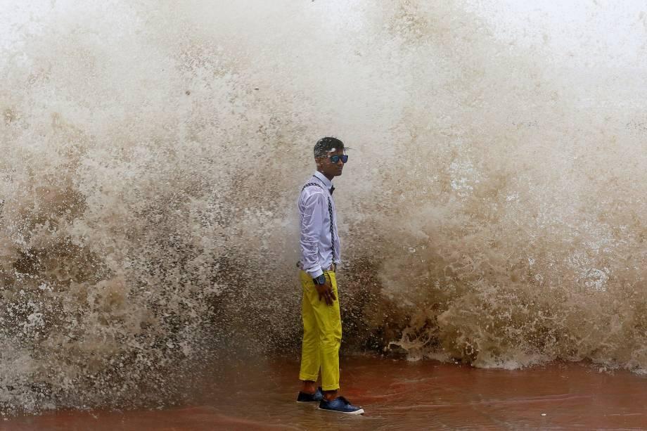 Jovem posa para uma fotografia durante uma maré alta em Mumbai, na Índia - 27/06/2017