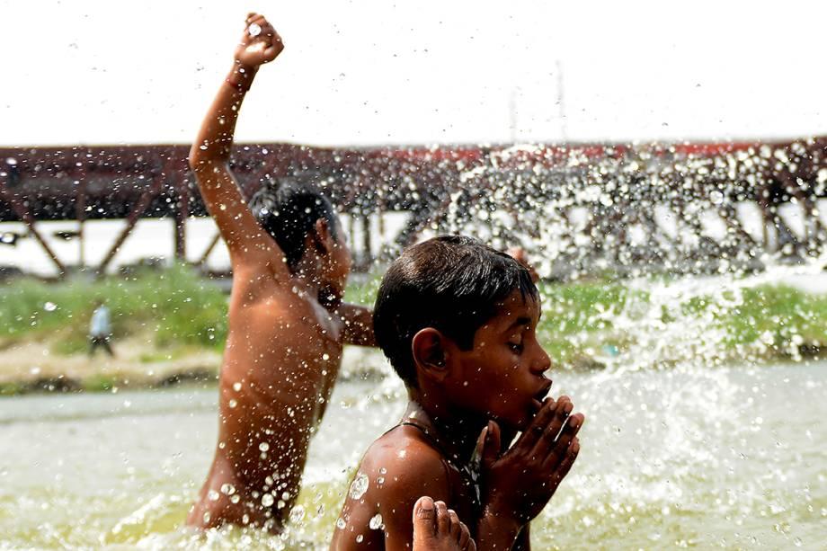 Garotos brincam em um grande lago em Nova Délhi, durante um dia quente com temperaturas registradas acima de 40 graus Celsius, na Índia - 05/06/2017
