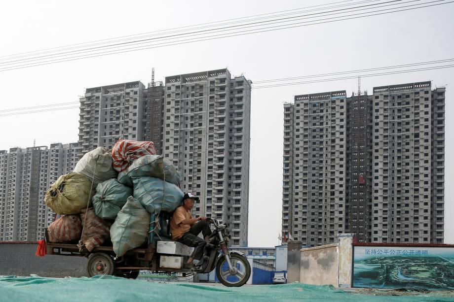 Homem pilota um triciclo carregado com sacos de material de reciclável em frente a um canteiro de obras em Pequim, na China - 27/06/2017