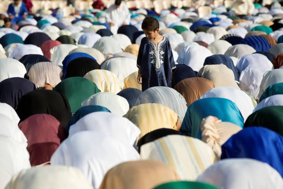 Menino observa a oração de fiéis muçulmanos durante o Eid al-Fitr data que marca o fim do mês sagrado de jejum do Ramadã, no enclave norte-africano de Ceuta - 26/06/2017
