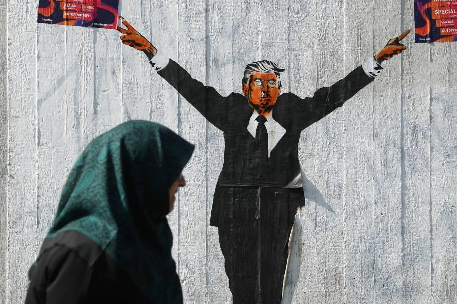 Mulher muçulmana passa em frente a uma representação do presidente dos Estados Unidos, Donald Trump, em Berlim, na Alemanha - 27/06/2017