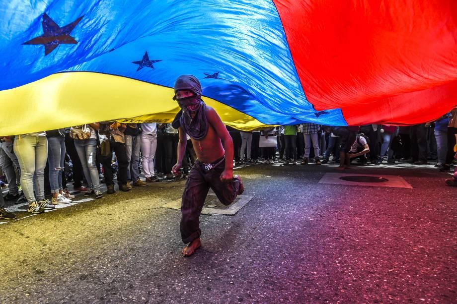 Menino corre sob uma bandeira venezuelana durante protesto de jornalistas e trabalhadores da mídia contra os recentes ataques à imprensa, em Caracas - 27/06/2017