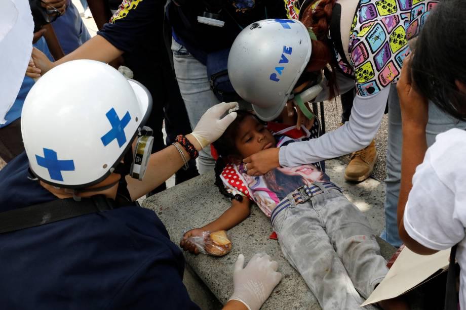 Criança afetada por gás lacrimogêneo é assistida por uma equipe de primeiros socorros durante manifestação contra o governo do presidente Nicolás Maduro, em Caracas, na Venezuela - 14/06/2017