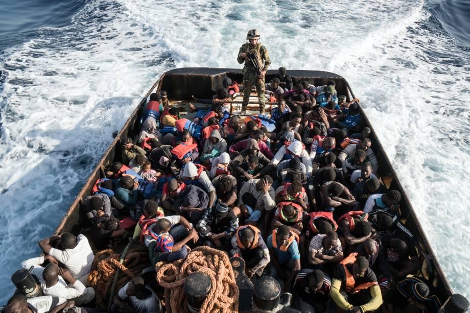 Soldado da guarda costeira da Líbia acompanha um barco com 147 imigrantes ilegais que tentavam chegar à Europa a partir da cidade costeira de Zawiyah, a oeste de Trípoli - 27/06/2017