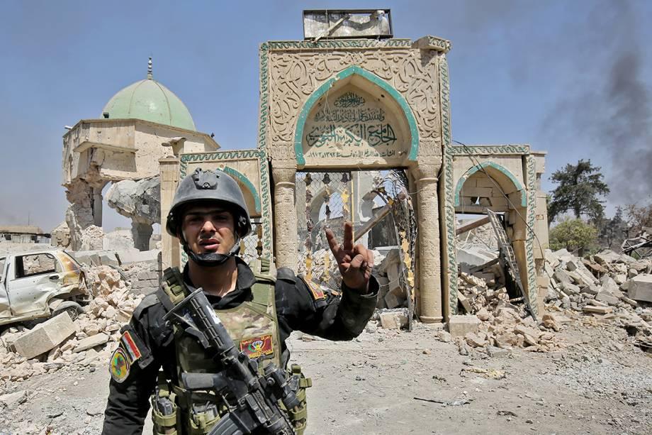 Membro do Esquadrão Anti-Terrorismo do Iraque posa para foto em frente a uma mesquita destruída na Cidade Velha de Mosul - 30/06/2017