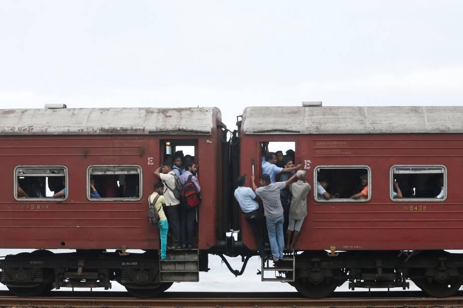 Pessoas viajam penduradas em um trem lotado para chegar ao trabalho em Colombo, no Sri Lanka - 14/06/2017