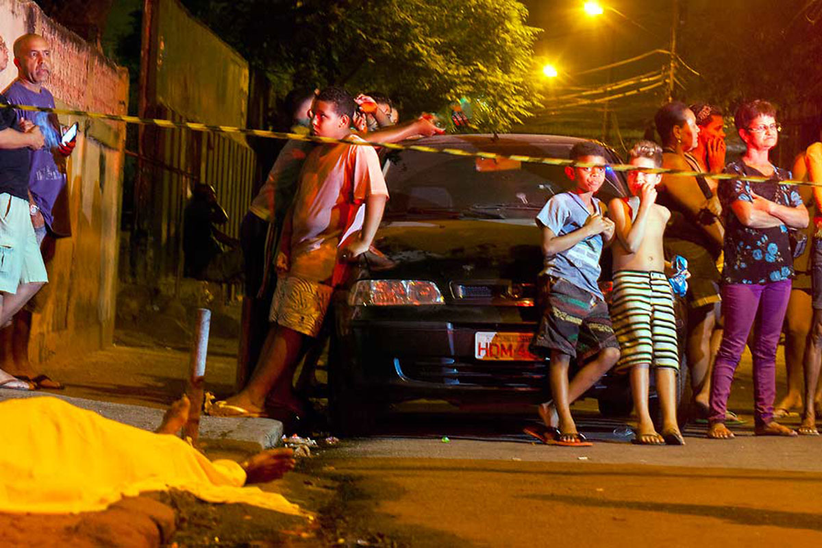 INDIFERENÇA – Crianças observam com naturalidade o corpo fuzilado em uma rua de Realengo: tão comum é a cena de cadáveres por recolher que as pessoas vão estabelecendo uma macabra convivência com a morte