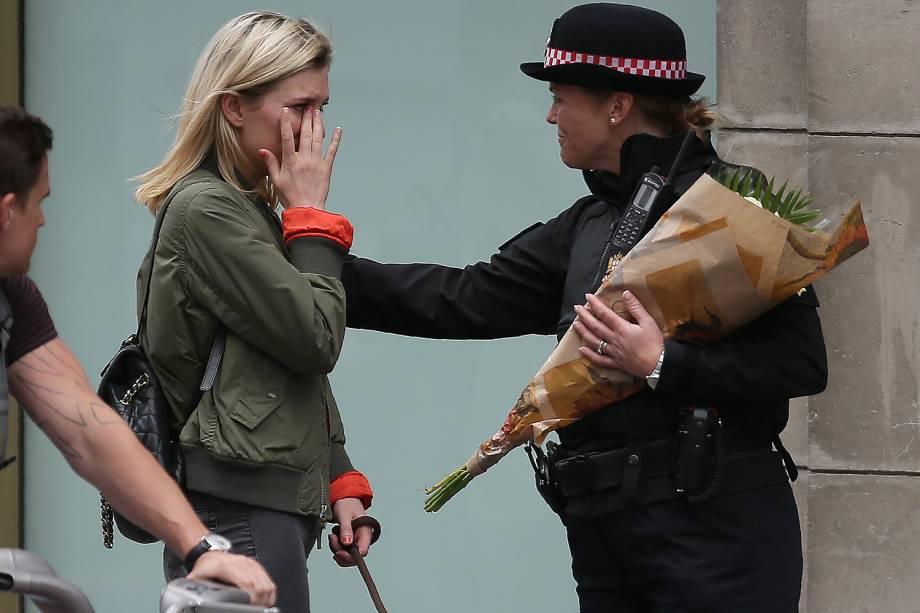 Mulher chora ao levar flores ao local do atentado na London Bridge - 04/06/2017