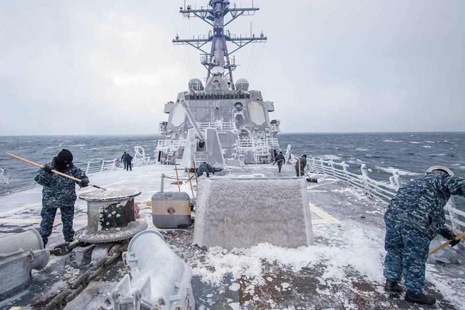 Marinheiros retiram neve do navio de guerra USS McCampbell, durante patrulhamento no mar do Japão