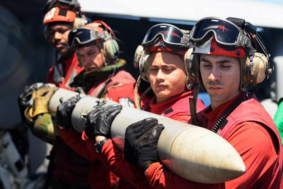 Fuzileiros navais do porta-aviões USS Nimitz descarregam mísseis de um caça, durante treinamento militar, no Oceano Pacífico