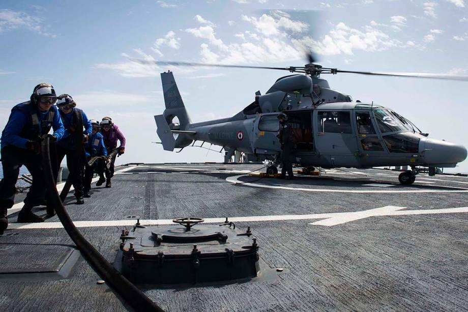 Fuzileiros navais puxam mangueira para reabastecer um helicóptero durante operação militar no destroyer USS Ross, no Mar Mediterrâneo