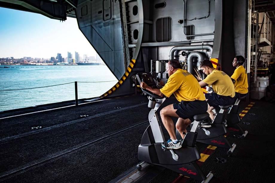 Marinheiros realizam treino físico a bordo do porta-aviões USS Theodore, em San Diego