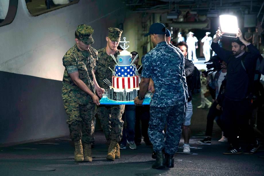 Marinheiros e fuzileiros navais carregam um bolo feito pelo programa 'Cake Boss', no navio de assalto anfíbio USS Kearsarge, em Nova York