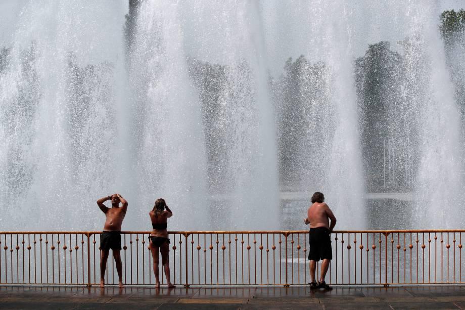 Pessoas desfrutam da água na fonte do parque Battersea, em Londres, para se refrescar durante a onda de calor na europa - 21/06/2017