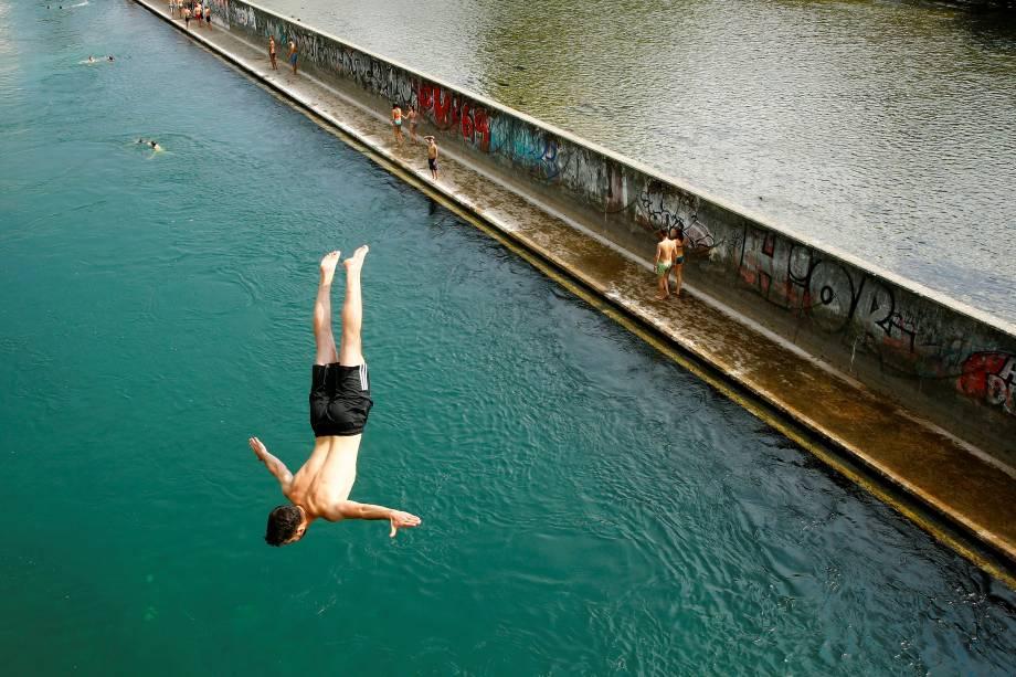 Homem salta de uma ponte direto para o rio Limmat, aproveitando as altas temperaturas do verão europeu, em Zurich na Suíça - 21/06/2017