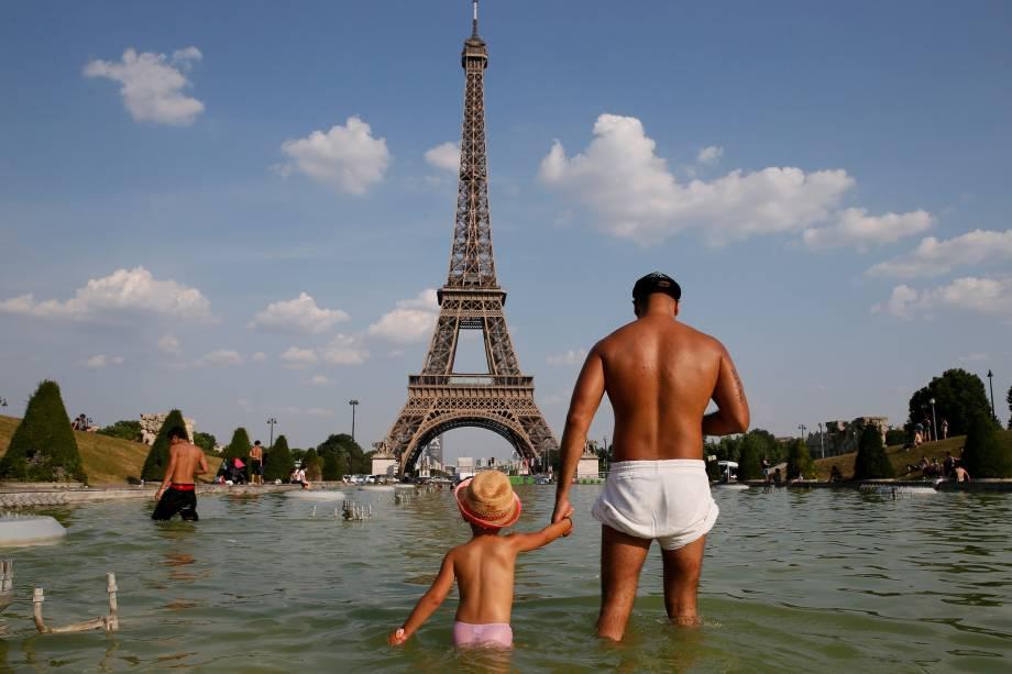 Homem segura a mão de uma criança enquanto se refrescam na fonte Trocadero, perto da torre Eiffel em Paris, na França - 21/06/2017