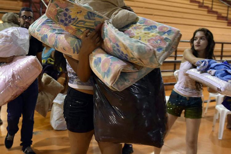 Pessoas ajudam com doações para a população afetada pela enxurrada de lama