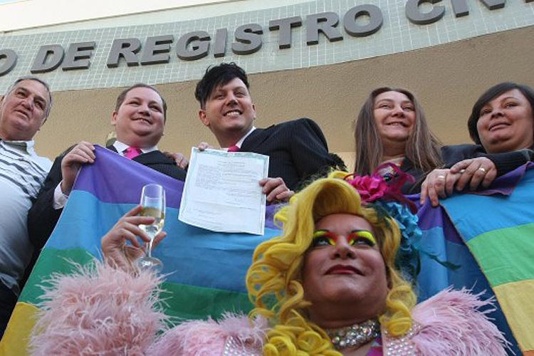 O comerciante Luiz André, de 37 anos, e o cabeleireiro José Sérgio, de 29 anos, ambos de terno preto, são o primeiro casal gay a obter a certidão de casamento civil no Brasil