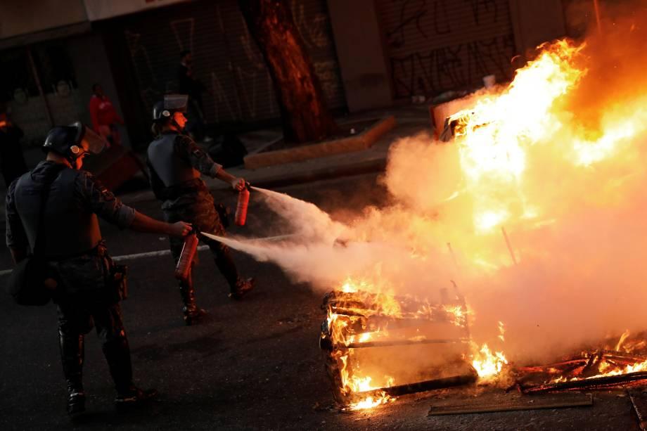 Policiais apagam barricada em chamas feita por manifestantes durante protesto contra as reformas econômicas propostas pelo presidente Michel Temer nesta manhã em São Paulo.