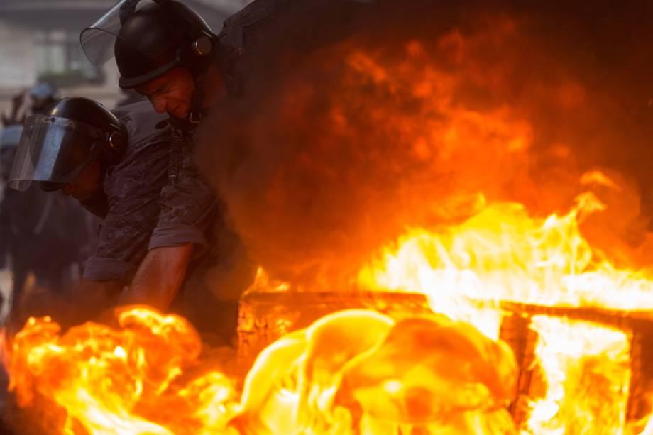 Policiais tentam apagar barricada em chamas feita por manifestantes durante protesto contra as reformas econômicas propostas pelo presidente Michel Temer em São Paulo.