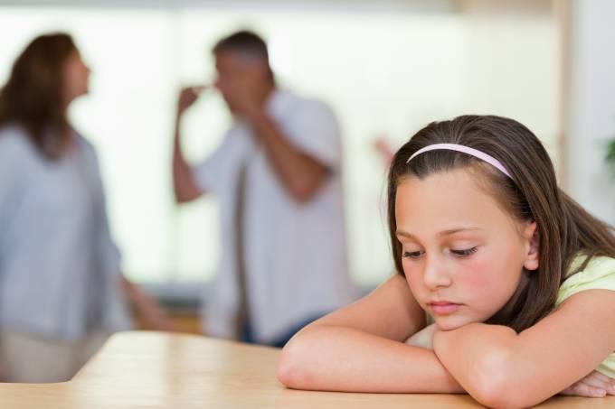 Criança triste com a briga dos pais