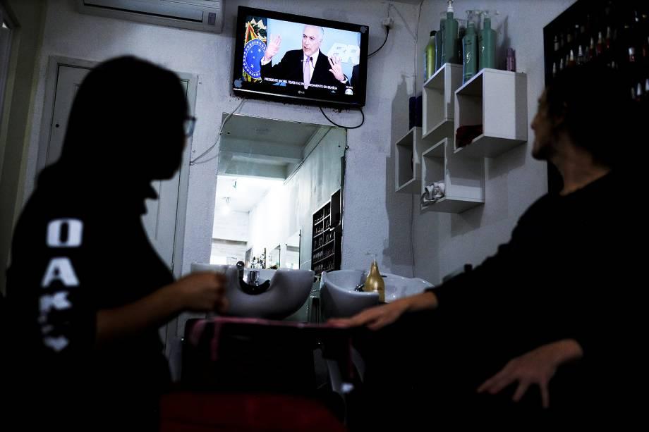 Pessoas assistem em um salão de beleza de São Paulo, o discurso do presidente Michel Temer em uma das TVs do estabelecimento - 27/05/2017