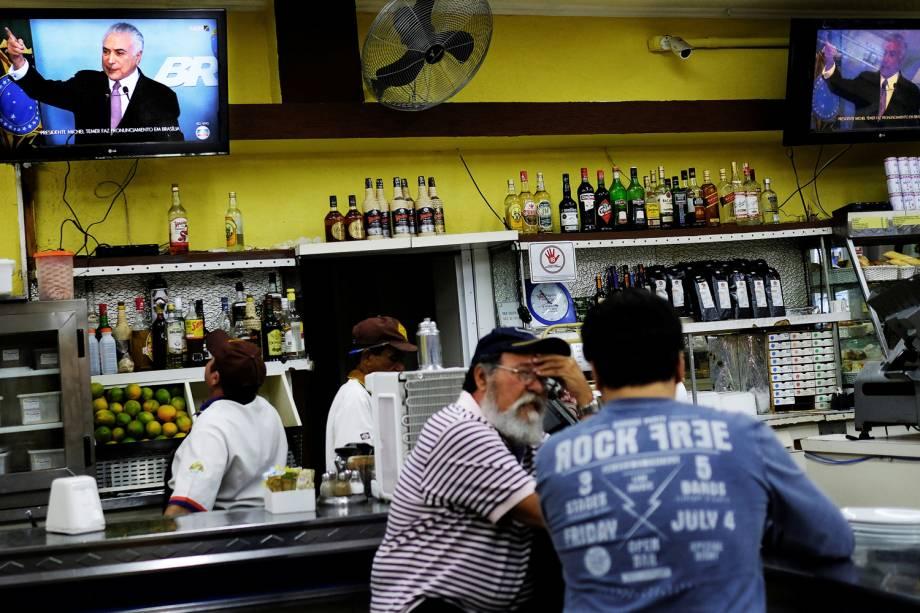 Pessoas assistem em um bar de São Paulo, o discurso do presidente Michel Temer em uma das TVs do estabelecimento - 27/05/2017