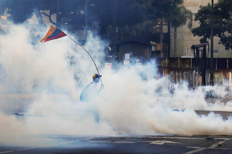Homem segura uma bandeira durante protestos contra o governo do presidente da Venezuela, Nicolas Maduro, em Caracas - 14/06/2017